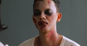 Maquilleur appliquant le maquillage de zombi sur le visage de l'homme banque de vidéos