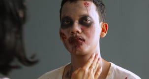 Maquilleur appliquant le maquillage fantasmagorique de Halloween banque de vidéos