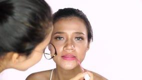 Maquilleur appliquant le rouge à lèvres sur des lèvres de femme banque de vidéos