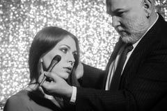Maquilleur professionnel travaillant avec la belle jeune femme, soins de la peau image libre de droits