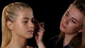 Maquilleur s'appliquant le maquillage à la jeune fille blonde noir closeup banque de vidéos