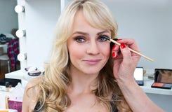 Maquilleur travaillant aux sourcils de femme Images libres de droits