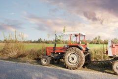 Maquinaria agrícola no primeiro plano que realiza o trabalho no campo Fotos de Stock Royalty Free