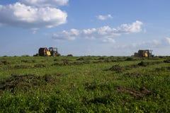 Maquinaria agr?cola, un tractor que recoge la hierba en un campo contra un cielo azul Haga heno la cosecha, cosecha de la hierba  foto de archivo libre de regalías