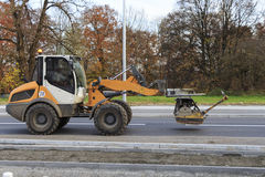Maquinaria de construcción del transporte del excavador en la calle en Munich Imágenes de archivo libres de regalías