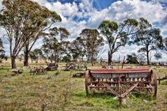 Maquinaria de granja vieja en campo Fotos de archivo libres de regalías