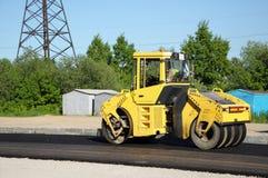 Maquinaria de rolamento amarela que pavimenta uma estrada Fotos de Stock Royalty Free
