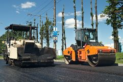 Maquinaria del pavimento del asfalto en el trabajo foto de archivo