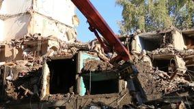 Maquinaria hidráulica da máquina escavadora do triturador que trabalha na casa velha da demolição Moscovo, Rússia video estoque