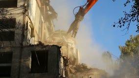 Maquinaria hidráulica del excavador de la trituradora que trabaja en casa vieja de la demolición Moscú, Rusia metrajes