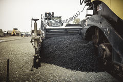 Maquinaria que coloca o asfalto ou o betume fresco durante a construção de estradas no terreno de construção vintage, efeito retr imagens de stock