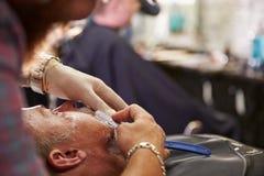 Maquinilla de afeitar de la garganta de Barber Shaving Client With Cut Fotos de archivo