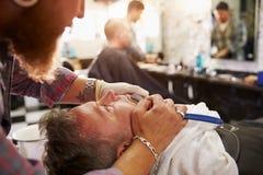 Maquinilla de afeitar de la garganta de Barber Shaving Client With Cut Imagenes de archivo