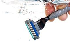 Maquinilla de afeitar en agua Imágenes de archivo libres de regalías