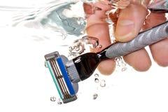 Maquinilla de afeitar en agua Imagen de archivo