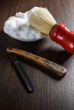 Maquinilla de afeitar vieja con la brocha de afeitar y la espuma Imagen de archivo