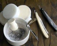 Maquinillas de afeitar rectas con el fondo de la taza y de la crema Fotografía de archivo