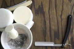 Maquinillas de afeitar rectas con el fondo de la taza y de la crema Foto de archivo