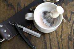 Maquinillas de afeitar rectas con la taza y la crema Fotos de archivo libres de regalías