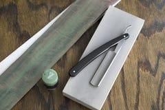 Maquinillas de afeitar rectas con la taza y la crema Foto de archivo