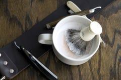 Maquinillas de afeitar rectas con la taza y la crema Imagenes de archivo