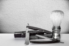Maquinillas de afeitar viejas y brocha de afeitar en fondo en blanco y negro Imagen de archivo libre de regalías