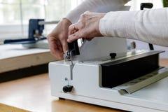 Maquinista de atascamiento de libro Trabajo con la m?quina de atascamiento de libro imágenes de archivo libres de regalías