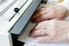 Maquinista de atascamiento de libro Trabajo con la m?quina de atascamiento de libro foto de archivo