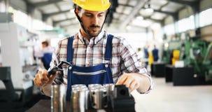 Maquinista industrial moderno que trabaja en fábrica foto de archivo
