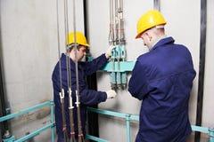 Maquinistas que ajustan la elevación en el elevador hoistway Imagen de archivo libre de regalías