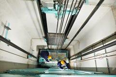 Maquinistas que ajustan la elevación en el elevador hoistway Fotografía de archivo