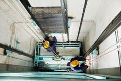 Maquinistas que ajustan la elevación en el elevador hoistway Fotos de archivo libres de regalías