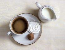 Marängkakor och en kopp kaffe med kräm Arkivfoto