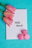 março da etiqueta olá! com as três tulipas cor-de-rosa e os três bolinhos de amêndoa cor-de-rosa Fotos de Stock