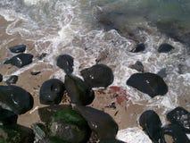 Maré entrante e pedregulhos pretos Imagens de Stock Royalty Free