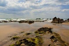 Maré entrante na areia e nas rochas Foto de Stock Royalty Free