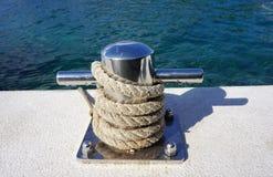 Maré natural da corda em torno de amarrar postes de amarração pela superfície azul do mar da cor imagem de stock