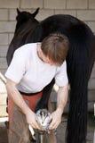 Maréchal-ferrant avec le cheval noir Image libre de droits