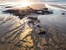 Marée basse formant les structures organiques dans le sable Photos libres de droits