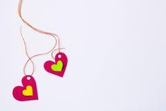 Marée de papier de deux coeurs à une ficelle sur un fond blanc Photos stock