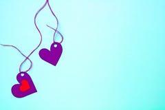 Marée de papier de deux coeurs à une ficelle sur un fond doucement bleu Image stock