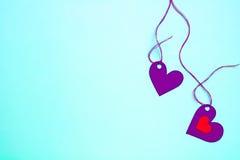 Marée de papier de deux coeurs à une ficelle sur un fond doucement bleu Photo libre de droits