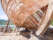 Marée inférieure et bateau motorisé en bois Photos libres de droits