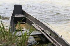 Marée inférieure et bateau motorisé en bois image stock