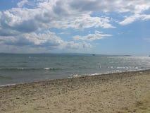 mar, arena, nubes y cielo Imágenes de archivo libres de regalías