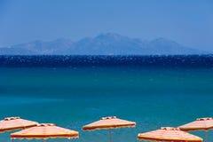 Mar azul e guarda-chuvas brilhantes imagem de stock