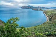 Mar azul hermoso, verdor en la orilla y montañas en el fondo Fotos de archivo libres de regalías