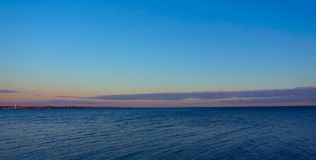 Mar azul llano contra el cielo azul Imagen de archivo libre de regalías