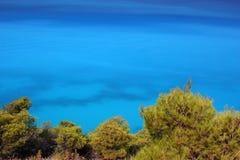 Mar azul y pinos verdes Imagenes de archivo