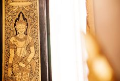 Golden buddhist mural painting at gate of Wat Trimitr Bangkok, T stock photography